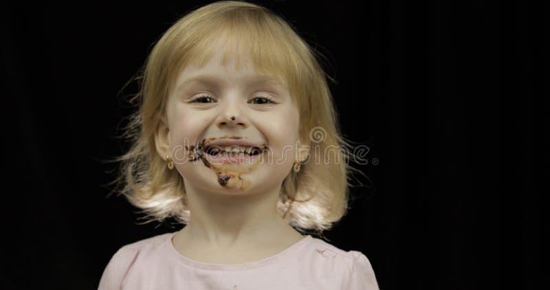 Kind isst geschmolzene Schokolade und Schlagsahne Schmutziges Gesicht lizenzfreie stockfotos
