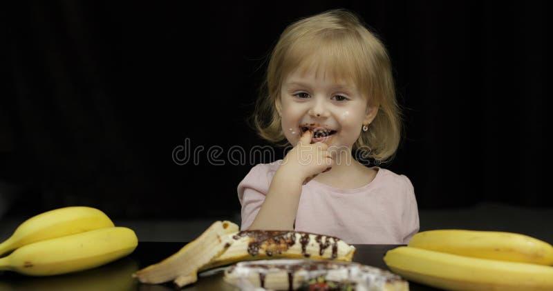 Kind isst geschmolzene Schokolade und Schlagsahne Schmutziges Gesicht stockbild