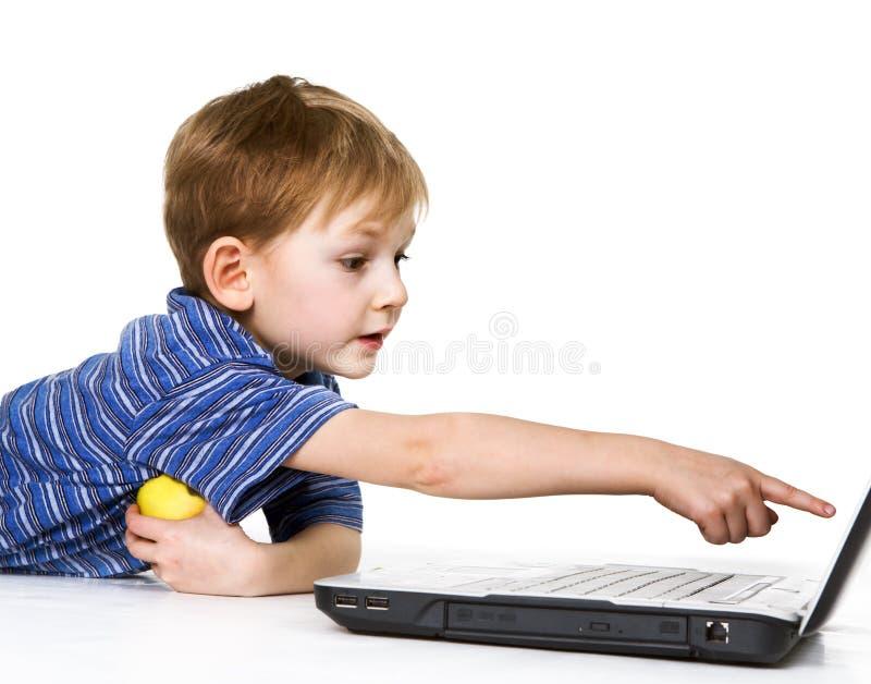 Kind ist auf einem Computerspiel scharf stockfotografie