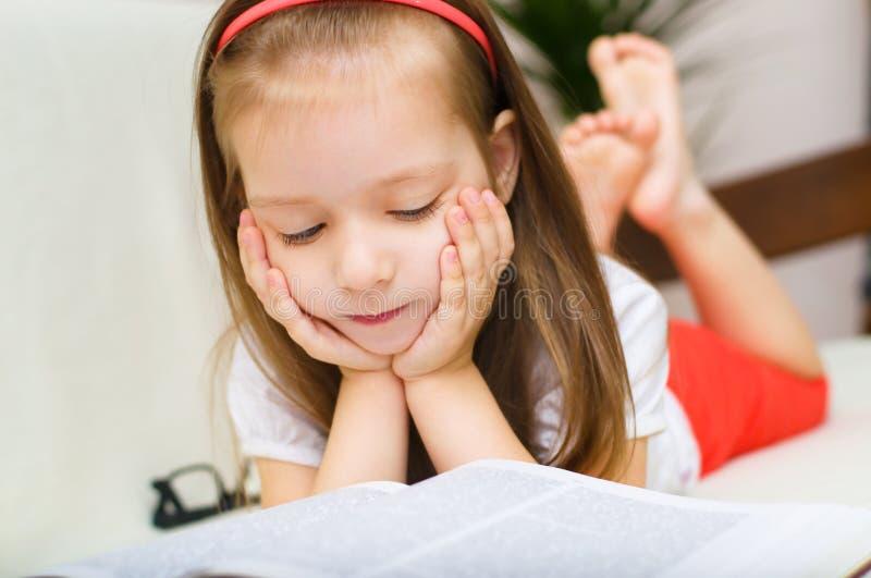 Kind ist Lesebuch beim Lügen auf einer Couch lizenzfreie stockfotografie
