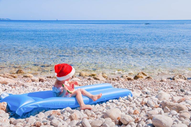 Kind in Kerstmanhoed op het strand stock afbeelding