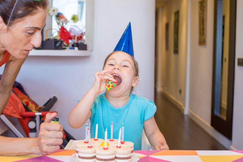 Kind klaar om partijventilator naast moeder en cake te blazen royalty-vrije stock afbeelding