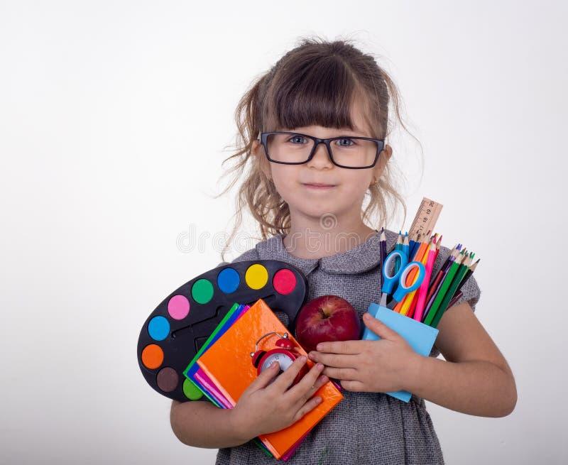 Kind Klaar voor School Leuk slim kind die in oogglazen schoollevering houden: pennen, notitieboekjes, schaar en appel stock foto