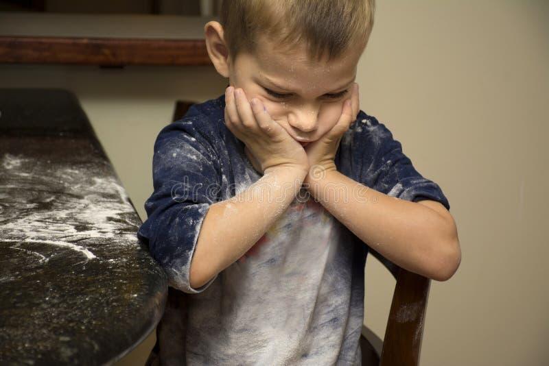 Kind knorrig na het helpen te bakken stock afbeelding