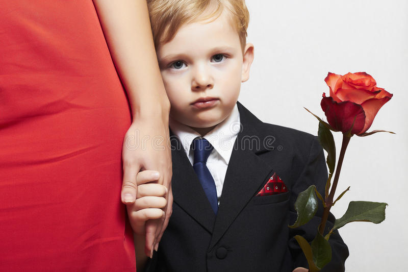 Kind in kostuum met moeder. bloem. rode kleding. familie. modieus weinig jongen. rood nam toe. neem de hand stock foto