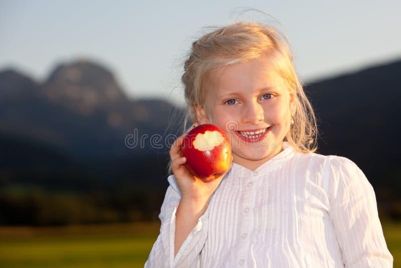Kind lächelt glückliche Außenseite mit rotem Apfel lizenzfreie stockbilder