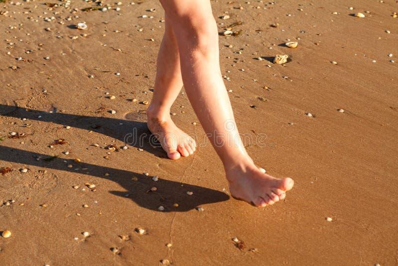 Kind läuft auf der Brandung auf dem Strand im Wasser lizenzfreies stockbild