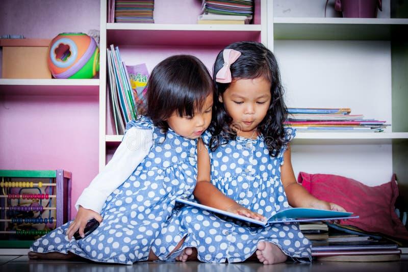 Kind las, Buch mit zwei nettes kleinen Mädchen Lesezusammen auf Büchern stockbilder