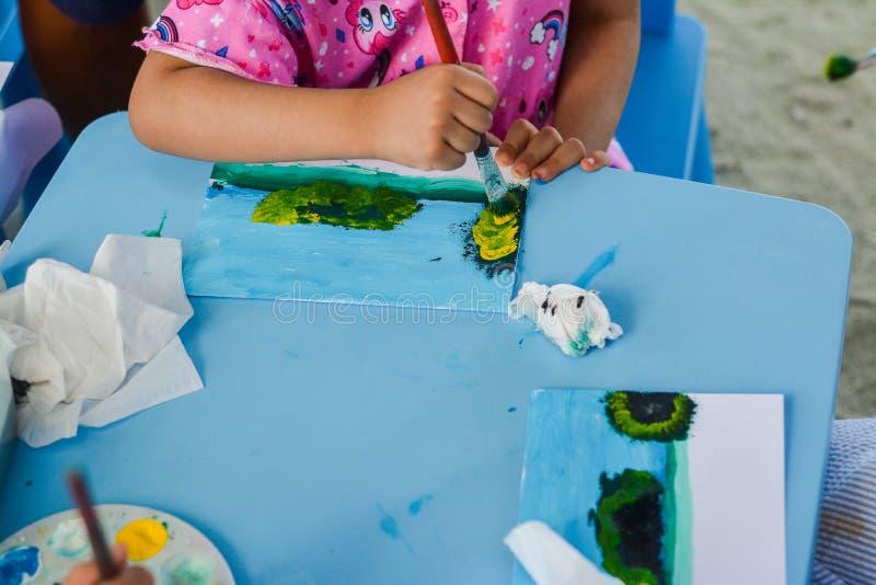 Kind lernt, wie man tropisches Landschaftsbild während der malenden Vorlagenklasse malt stockfoto