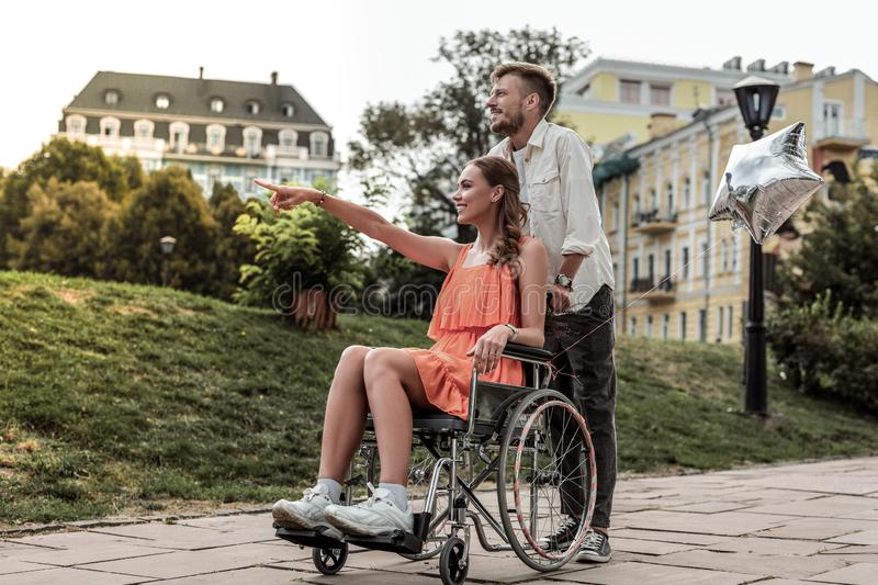 Kind longhaired girl expressing positivity during walk. Romantic mood. Charming female person sitting on her wheelchair and talking with her boyfriend royalty free stock photo