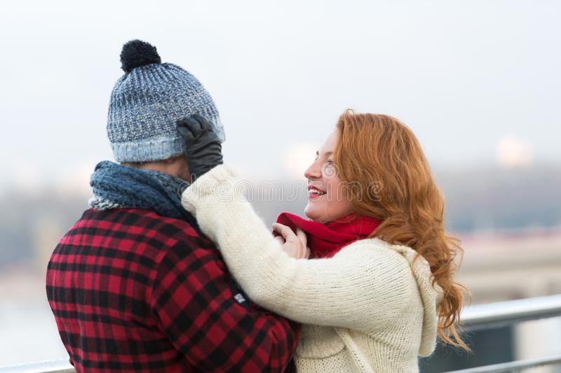 Caring woman putting warm hat on her husband. Kind loving women smiling while being outdoors in cold weather and touching the hat on the head of her beloved man stock photos