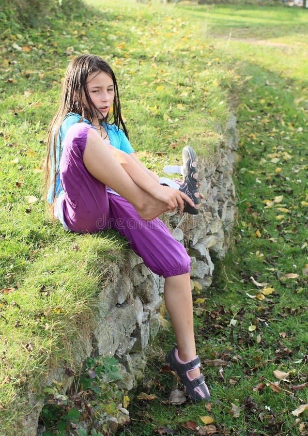 Kind - Mädchen, das auf Schuhe sich setzt lizenzfreie stockfotografie