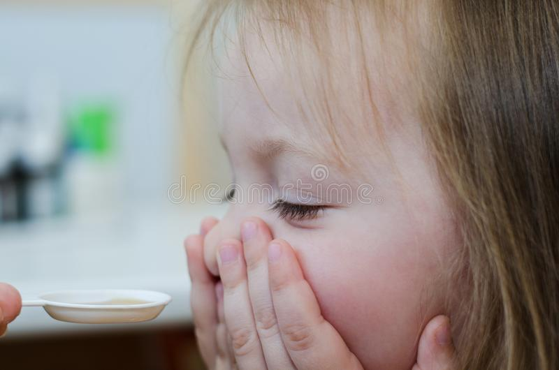 Kind möchte nicht Medizin trinken lizenzfreie stockfotos
