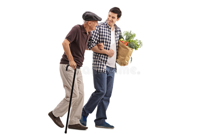 Kind man helping a senior with groceries. Kind young men helping a senior gentleman with his groceries isolated on white background royalty free stock photo