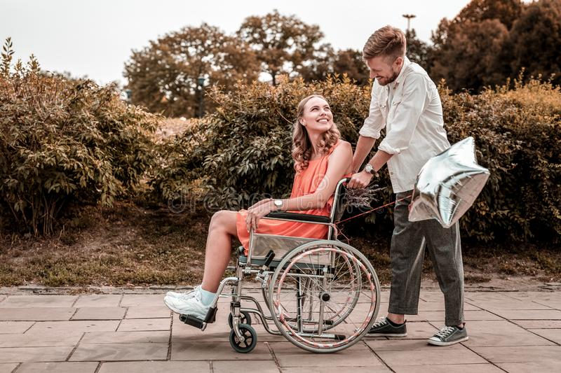 Kind man looking at his disabled girlfriend while pushing her wheelchair royalty free stock images
