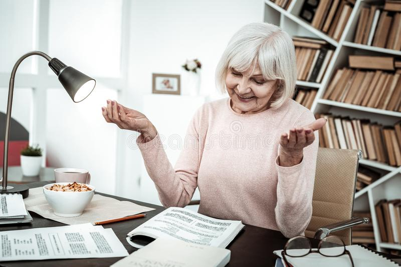 Kind mature female person looking at her notes royalty free stock photos