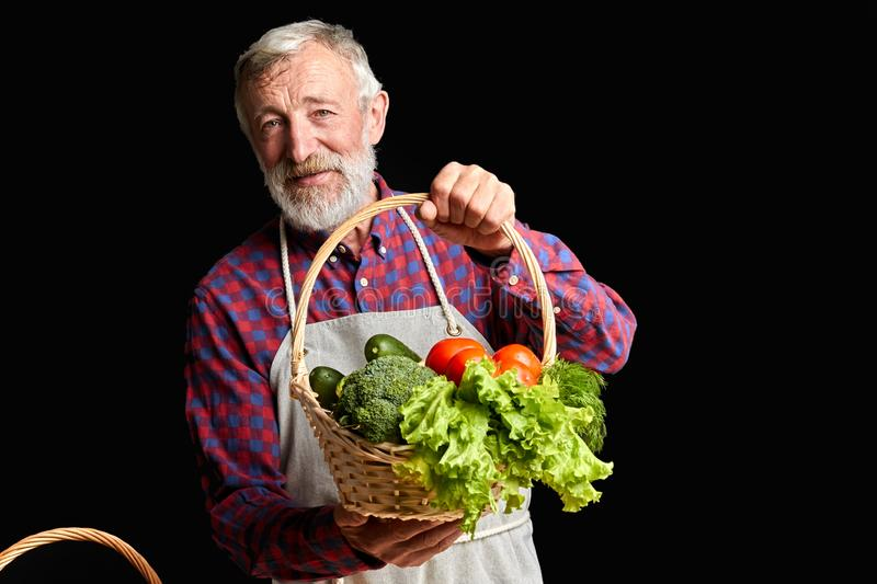 Kind mature village man picked up from greenhouse some fresh vegetables stock images