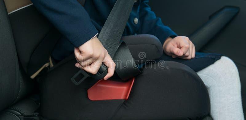 Kind-meisje in een kindzetel, klemmen onafhankelijk, zijnd in de auto, vóór de reis stock afbeelding