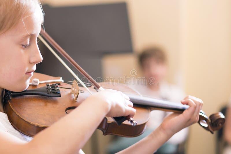 Kind, meisje het spelen viool binnen in muziekklasse De ruimte van het exemplaar stock fotografie