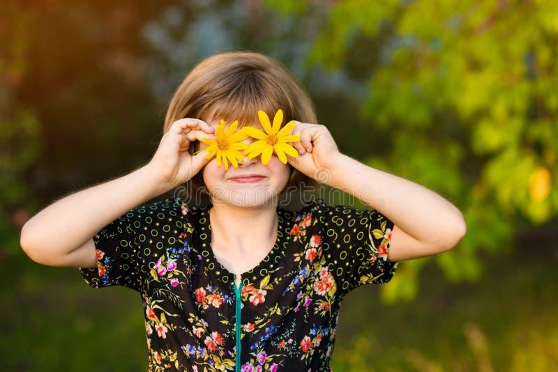 Kind met bloemenogen in groen park stock foto
