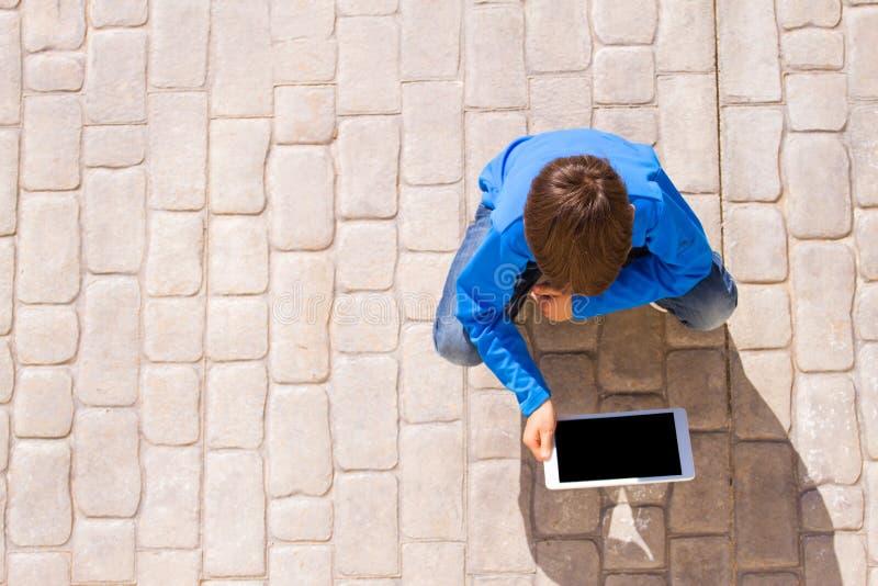 Kind met de zitting van de tabletcomputer in openlucht Hoogste mening stock foto