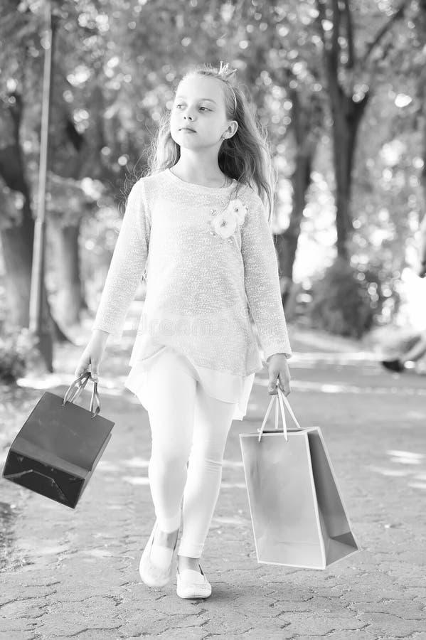 Kind met document zakken in de zomer Meisje met het winkelen zakkengang in park Weinig prinses met kroon op lang blond haar royalty-vrije stock foto