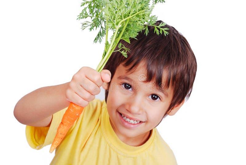 Kind met een in hand wortel stock fotografie