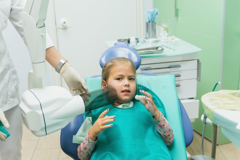 Kind met een moeder bij een tandarts` s ontvangst Het meisje ligt als voorzitter, achter haar moeder De artsenwerken met stock foto