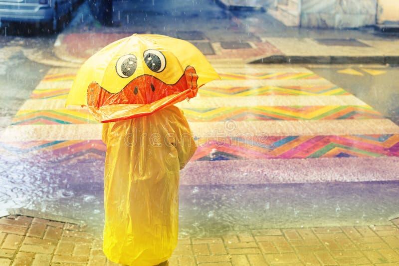 Kind met gele paraplu onder de doucheregen Jongen die gele regenjas draagt die van regenval geniet stock foto's