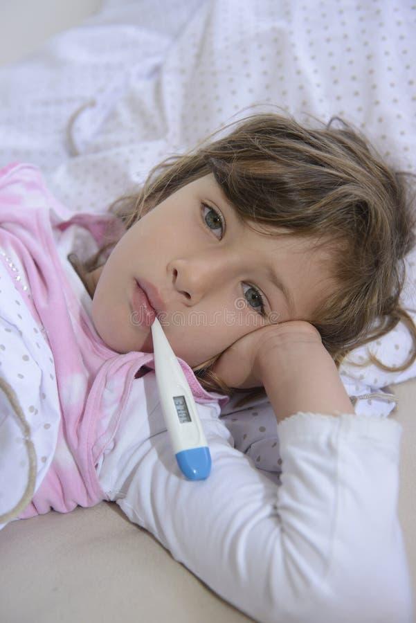 Kind met koorts in bed stock fotografie