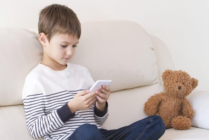 Kind met mobiele telefoon thuis Jongen spelen, het leren, die iets lezen royalty-vrije stock foto's