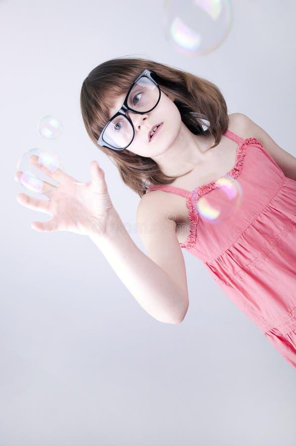 Kind met nerdglazen die met zeepbels plaing royalty-vrije stock fotografie