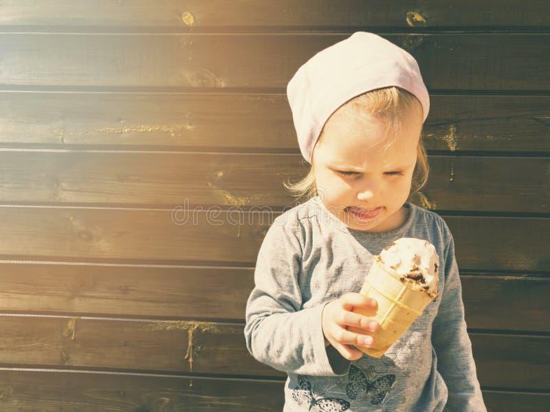 Kind met roomijs in hand op houten achtergrond royalty-vrije stock fotografie