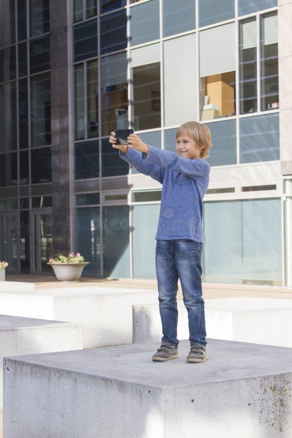 Kind met telefoon Jongen die het scherm, speelspelen bekijken, die apps gebruiken openlucht De technologievrije tijd van schoolme royalty-vrije stock afbeeldingen
