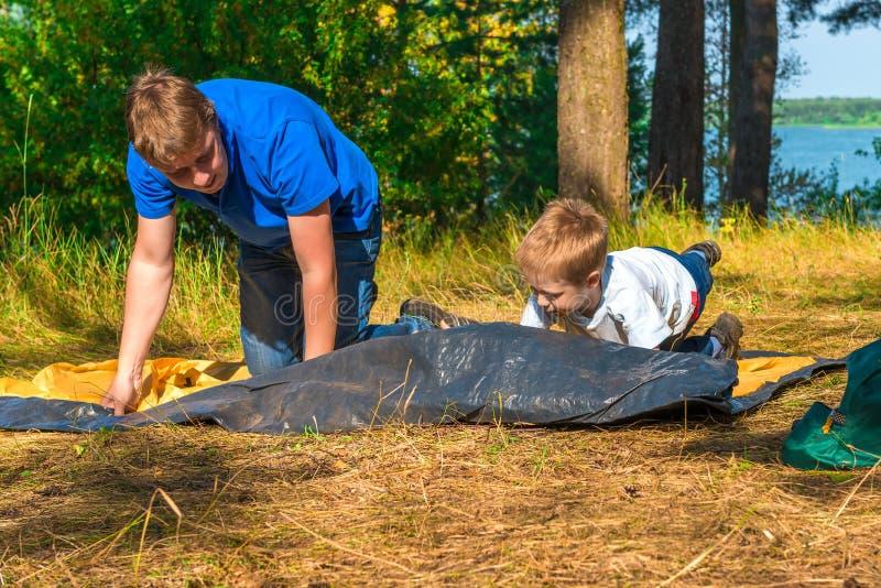 Kind met vader om tent te installeren stock foto's