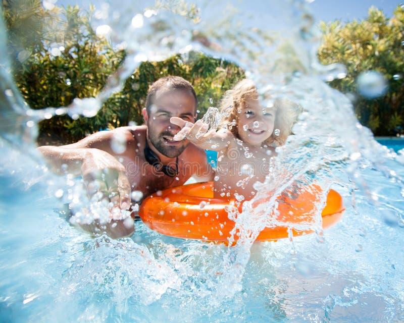 Kind met vader in zwembad stock afbeeldingen