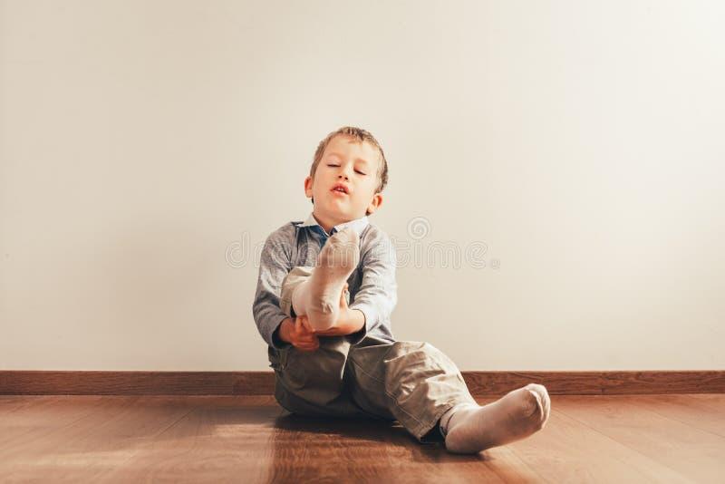 Kind met veel onafhankelijkheid op de vloer, dat zijn sokken op de grond zet met een uitdrukking van inspanning royalty-vrije stock fotografie
