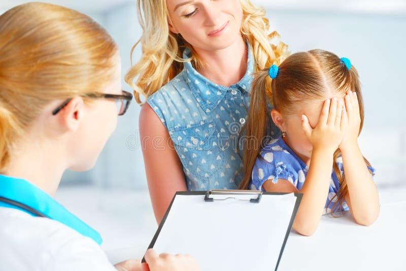 Kind met zijn moeder bang van bezoek aan arts stock foto