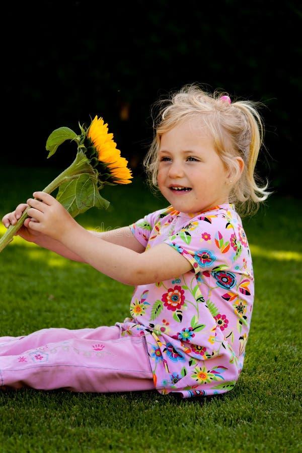 Kind met zonnebloemen in de tuin in de zomer stock foto