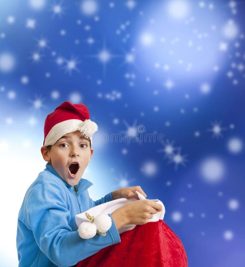 Kind mit Überraschungsausdruck mit Weihnachtsmann-Geschenk stockfotos