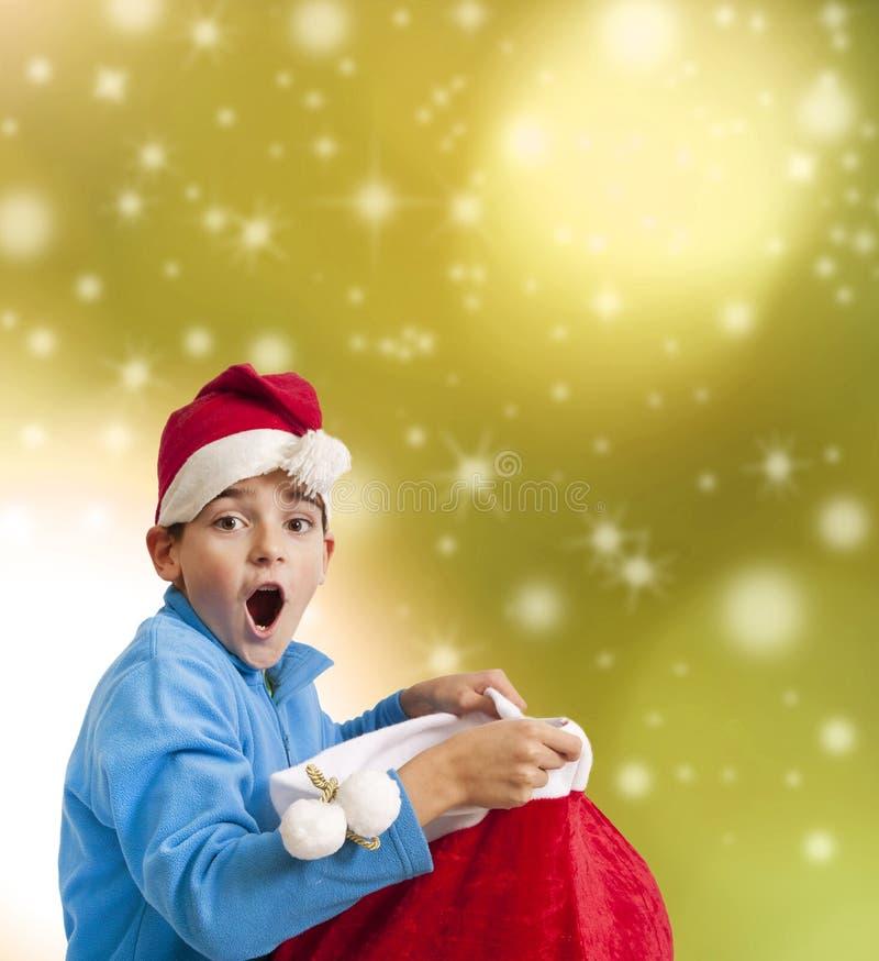 Kind mit Überraschungsausdruck mit Weihnachtsmann-Geschenk lizenzfreie stockfotos