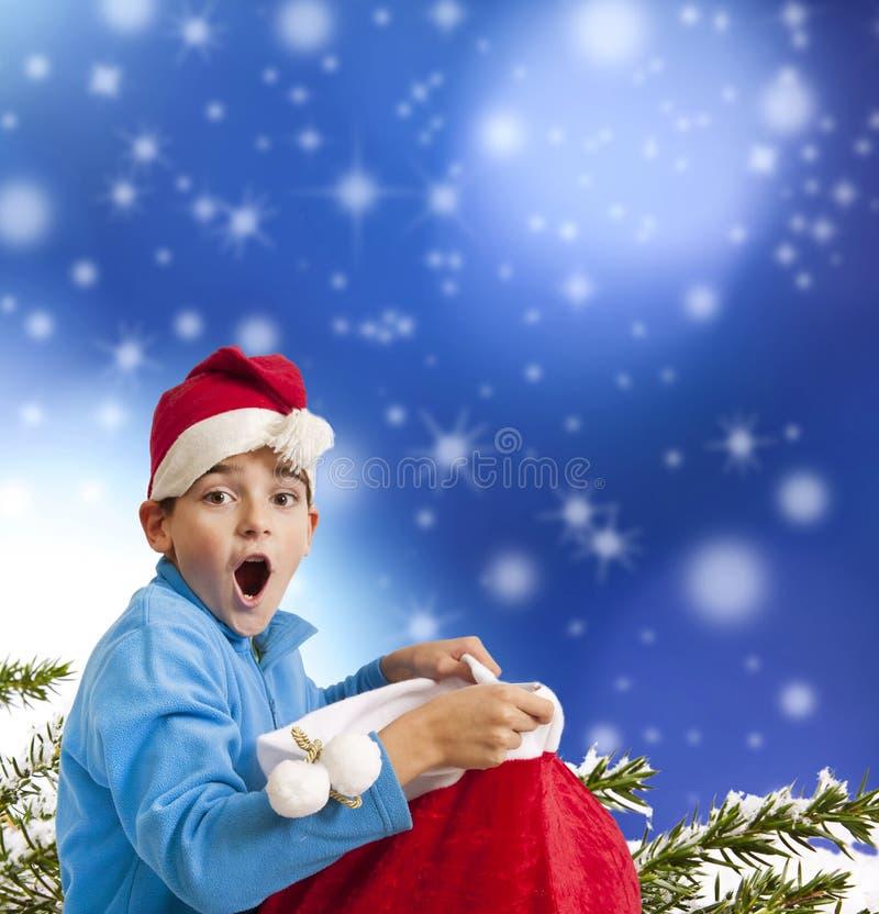 Kind mit Überraschungsausdruck mit Weihnachtsmann-Geschenk stockfotografie