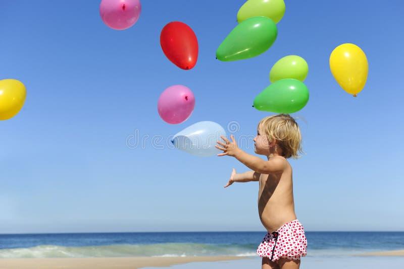 Kind mit Ballons auf dem Strand lizenzfreies stockfoto