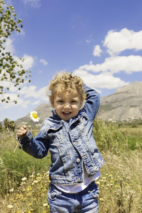 Kind mit Blume auf dem Gebiet stockbilder