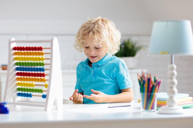 Kind mit dem Abakus, der die Hausarbeit nach der Schule tut lizenzfreies stockfoto