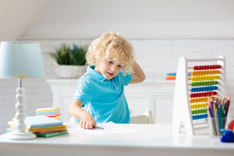 Kind mit dem Abakus, der die Hausarbeit nach der Schule tut lizenzfreie stockbilder