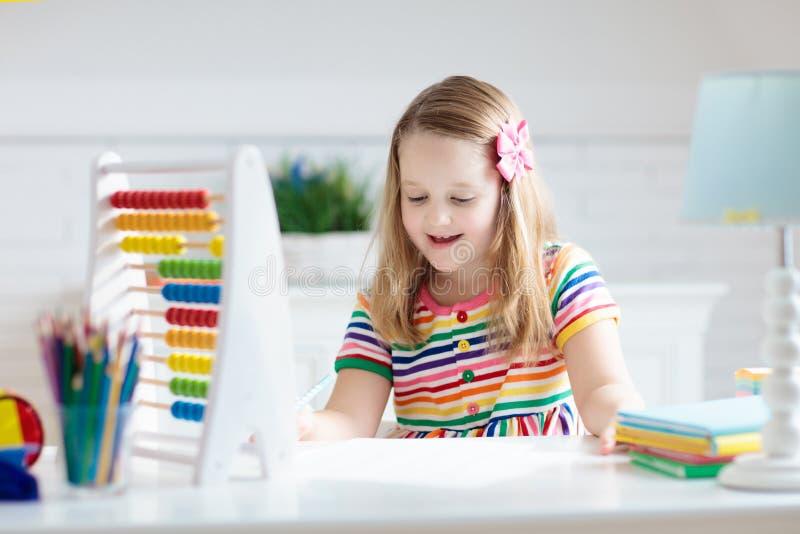 Kind mit dem Abakus, der die Hausarbeit nach der Schule tut stockfoto