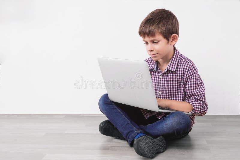 Kind mit dem Laptop, der auf dem Boden sitzt stockbilder