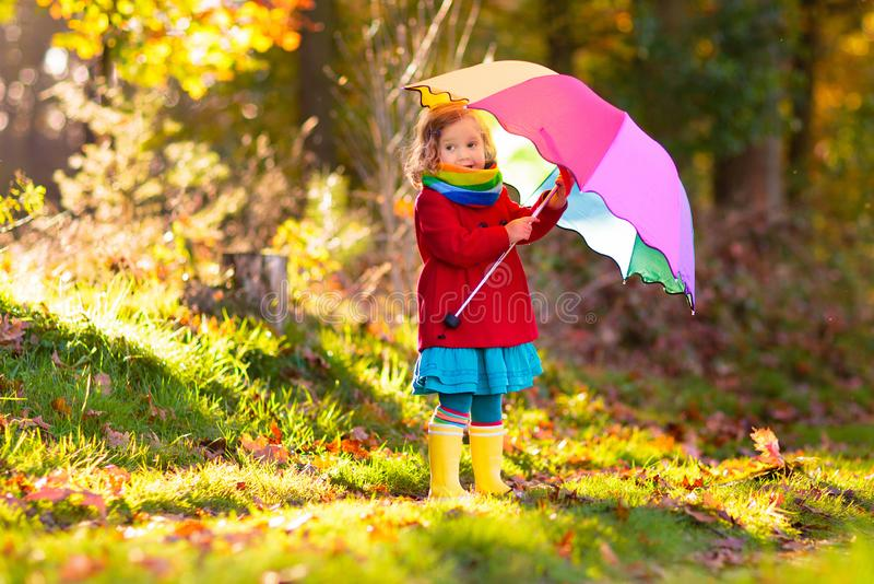 Kind mit dem Regenschirm, der im Herbstregen spielt stockfoto