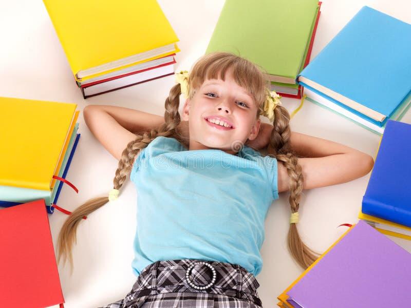 Kind mit dem Stapel des Buches liegend auf Fußboden. lizenzfreies stockbild